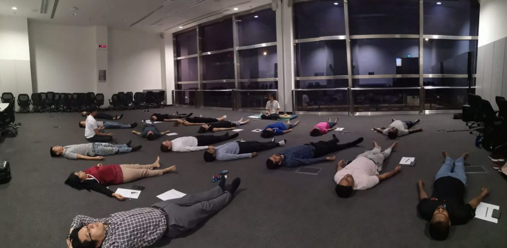 20 people lying down at deep relaxation meditation - Xuan Healing Cove