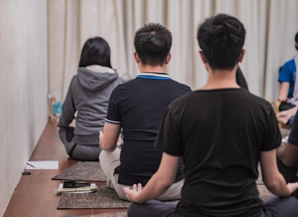 Back view of three people in a large group meditating at Xuan Healing Cove's collaboration session on Abundance Drumming